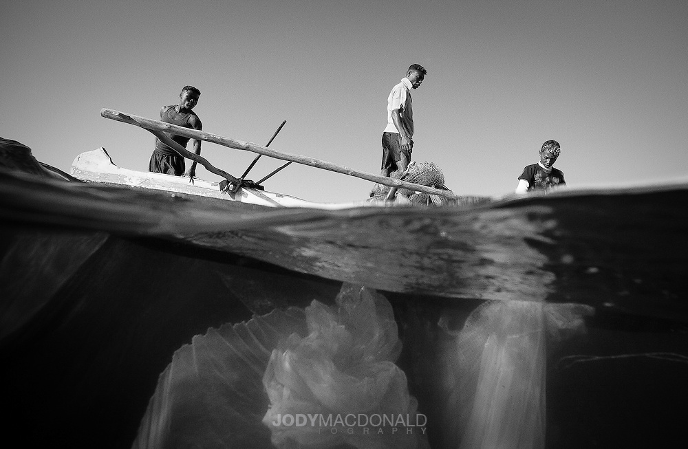 Black and white of Local Vezo fishermen deploy their nets from their handmade canoe in hopes of catching small fish for their families.  A practice that has changed little in hundreds of years.