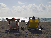 two people relaxing in a chair on the beach Miami USA