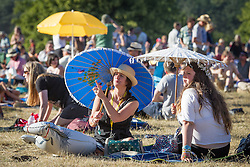 © Licensed to London News Pictures . 19/07/2013 . Suffolk , UK . Women shade themselves from the bright sunshine beneath parasols . The Latitude music and culture festival in Henham Park , Southwold . Photo credit : Joel Goodman/LNP