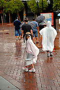 Child (6 years old) wearing Akubra bush-hat over plastic raincoat. Darling Harbour, Sydney, Australia