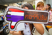 "09 DECEMBER 2012 - BANGKOK, THAILAND:   A Thai college student holds up a ""Thumbs Down on Corruption"" placard at the Bangkok Art and Culture Centre (BACC). About 1,500 Thai university students from 90 universities across Thailand attended the rally. The latest Corruption Perceptions Index survey by Transparency International listed Thailand at number 88 out of 176 countries surveyed. The level of corruption in Thailand is perceived to be on the same par as Malawi, Swaziland and Zambia. Thailand's ranking slipped from 80 last year. A series of surveys show that Thais increasingly view corruption as acceptable. A recent ABAC (Assumption Business Administration College, the forerunner to Assumption University, one of the most respected private universities in Thailand) poll reported that a majority (63 per cent) of Thai people hold the view that corruption in government is acceptable as long as they also benefit from it. A majority of young people under 20 now hold the same attitude. International Anti-Corruption Day has been observed annually, on the 9th December, since the passage of the United Nations Convention Against Corruption on 31 October 2003.      PHOTO BY JACK KURTZ"
