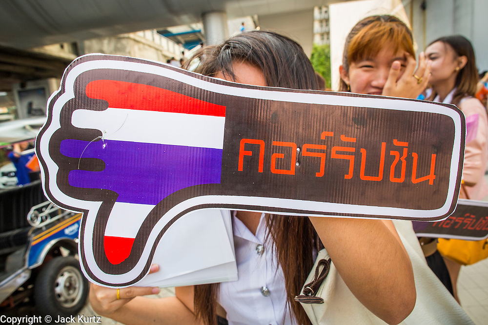 """09 DECEMBER 2012 - BANGKOK, THAILAND:   A Thai college student holds up a """"Thumbs Down on Corruption"""" placard at the Bangkok Art and Culture Centre (BACC). About 1,500 Thai university students from 90 universities across Thailand attended the rally. The latest Corruption Perceptions Index survey by Transparency International listed Thailand at number 88 out of 176 countries surveyed. The level of corruption in Thailand is perceived to be on the same par as Malawi, Swaziland and Zambia. Thailand's ranking slipped from 80 last year. A series of surveys show that Thais increasingly view corruption as acceptable. A recent ABAC (Assumption Business Administration College, the forerunner to Assumption University, one of the most respected private universities in Thailand) poll reported that a majority (63 per cent) of Thai people hold the view that corruption in government is acceptable as long as they also benefit from it. A majority of young people under 20 now hold the same attitude. International Anti-Corruption Day has been observed annually, on the 9th December, since the passage of the United Nations Convention Against Corruption on 31 October 2003.      PHOTO BY JACK KURTZ"""