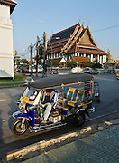 The tuk-tuk is the Southeast Asian version of a vehicle known elsewhere as an auto rickshaw or cabin cycle. The tuk-tuk is widely used as urban transport here in Bangkok (and other Thai cities, as well as other major Southeast Asian and South Asian cities). In the background is Wat Pho (or Po), the oldest and largest wat (Buddhist temple or monastery) in Bangkok, with the longest reclining Buddha and the largest collection of Buddha images in Thailand. Wat Pho is located outside the south wall of the Grand Palace.