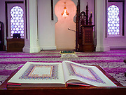 06 JUNE 2015 - KUALA LUMPUR, MALAYSIA: An open Koran in front of the mihrab at Masjid Jamek. A mihrab is a semicircular niche in the wall of a mosque that indicates the qibla (the direction to Mecca). Built in 1909, Jamek Mosque is one of the oldest mosques in Kuala Lumpur. It is located at the confluence of the Klang and Gombak River and was designed by Arthur Benison Hubback. The mosque was a built in the style of Mughal (northern India) architecture.  Before the national mosque, Masjid Negara, was opened in 1965, Masjid Jamek served as Kuala Lumpur's main mosque.     PHOTO BY JACK KURTZ