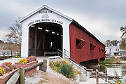 "Bridgeton Historic District, Indiana: Bridgeton Covered Bridge (245 feet long) was rebuilt in historically accurate Burr Arch style in 2006 over Big Raccoon Creek (replacing 1868 bridge burnt by arson in 2005) on Bridgeton Road, Parke County, Indiana, USA. Bridgeton Mill was established 1823, rebuilt 1870, and is the oldest continuously operating mill west of the Allegheny Mountains. The mill grinds wheat into flour and corn into meal with 200 year-old French Buhr stones. Red and white paint protects the wood bridge. The traditional ""Cross this bridge at a walk"" sign required slow vehicle speed, but traffic is now diverted to an adjacent modern bridge."