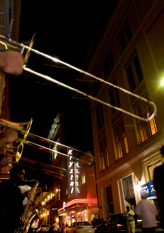 Three trombone players perform on Bourbon street. They are part of a young band that plays big band music on Bourban St. in New Orleans, LA.