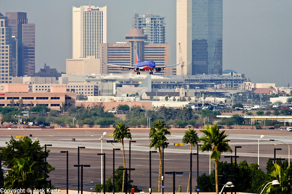 06 DECEMBER 2007 -- PHOENIX, AZ: A Southwest Airlines plane lands at Sky Harbor Airport. Sky Harbor International Airport is on the edge of downtown Phoenix, in the middle of the Phoenix metropolitan area. It is one of the largest airports in the country with more than 1,400 flights daily. The airport's proximity to downtown though, less than five miles from the city center, is both a blessing and a curse. It takes about 15 minutes to get to the airport from downtown, but a proposed 510 foot tall building proposed in downtown, near the airport flight path, has raised safety concerns. The Federal Aviation Administration wants the development capped at 355 feet. Similar concerns about a proposed football stadium in Tempe, which borders the east side of the airport, scuttled that project and led to the stadium being built in Glendale, about 30 miles from the airport.  PHOTO BY JACK KURTZ