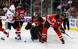 Jan 4, 2008; Newark, NJ, USA; Ottawa Senators center Mike Fisher (12) and New Jersey Devils defenseman Mike Mottau (27) battle after a save by New Jersey Devils goalie Scott Clemmensen (35) during the first period at the Prudential Center.