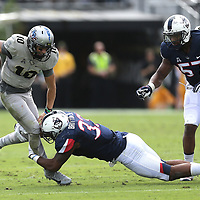 ORLANDO, FL - NOVEMBER 11: Chris Britton #33 of the Connecticut Huskies makes a tackle on McKenzie Milton #10 of the UCF Knightsduring a NCAA football game between the University of Connecticut Huskies and the UCF Knights on November 11, 2017 in Orlando, Florida. (Photo by Alex Menendez/Getty Images) *** Local Caption *** Chris Britton; McKenzie Milton