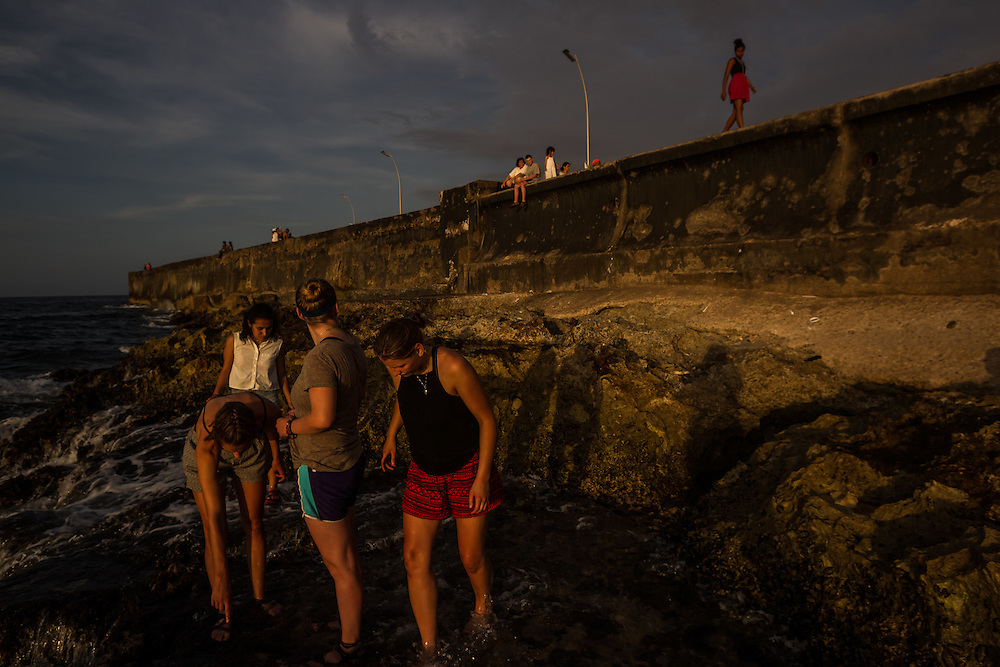 HAVANA, CUBA - JUNE 18, 2015:  American tourists explore the waterfront underneath the Malecon in Havana. After more than half a century defined by mistrust and rancor, the United States will officially reopen its six-story embassy in Havana on Monday, marking a watershed moment of transition for the two countries as they lean toward closer diplomatic ties and ease past one of the last remnants of the Cold War.   American tourists are expected to come in waves to experience a nation so long forbidden – there has already been a 26 percent increase in visitors since December. And there will also be families who can reunite without having to cross political minefields. PHOTO: Meridith Kohut for The New York Times