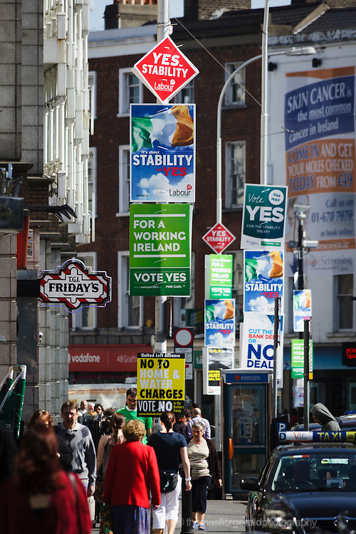 May 2012, Dublin City, Ireland: Referendum Posters cover every pole as people walk by underneath at the top of Dublin's busy Grafton Street and at the side of St. Stephen's Green