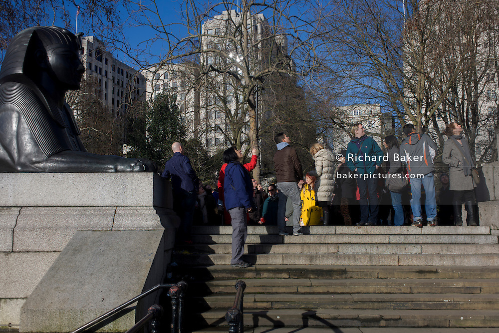A tour group organised by WalkLondon stop by a sphinx to hear about the ancient Egyptian obelisk known as Cleopatra's Needle, on the Embankment WC2. Cleopatra's Needle is flanked by two faux-Egyptian sphinxes cast from bronze that bear hieroglyphic inscriptions that say netjer nefer men-kheper-re di ankh (the good god, Thuthmosis III given life). These Sphinxes appear to be looking at the Needle rather than guarding it. This is due to the Sphinxes' improper or backwards installation.