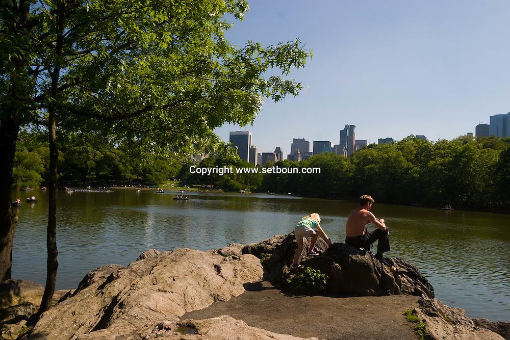New York. Central Park. tourists rowing on the lake, in the distance Manhattan cityscape  / touristes en barque ramant sur le lac de central park,