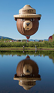 Hot air balloons are reflected in the water of Bald Eagle Lake during the Hot Air Balloon rodeo in Steamboat Springs, CO.