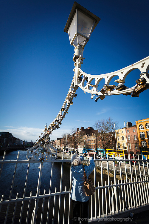 2012: Dublin, Ireland. Tourist taking a photograph on the ha'penny bridge in Dublin