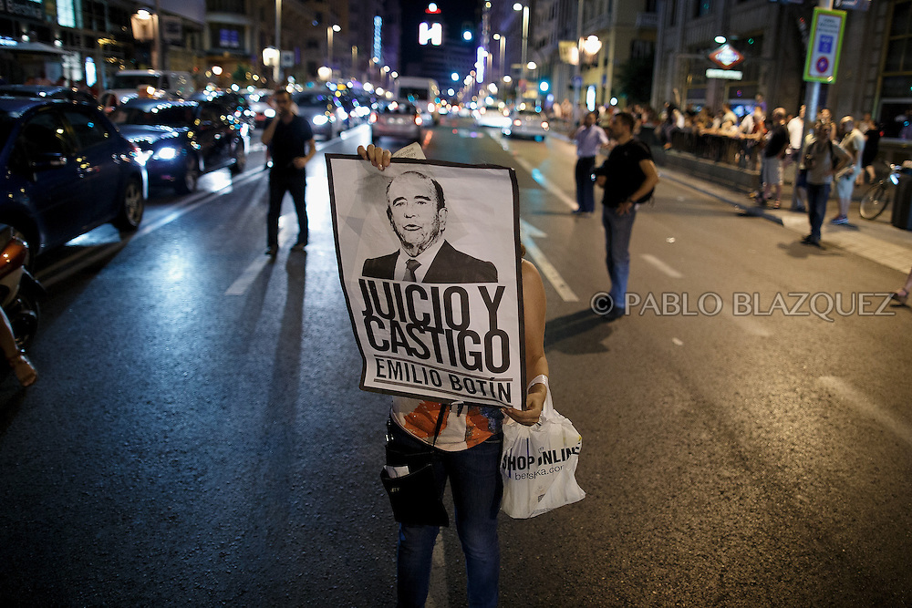 A protestors holds a placard reading 'Trial and punishment. Emilio Botin' at Gran Via during a demonstration against the Spanish government, on Thursday, July 18, 2013, in Madrid, Spain. Placard reads 'Rajoy liar. Go away now'. Thousands demonstrators demanding the resignation of Prime Minister Mariano Rajoy and its party gathered in front of the People's Party headquarter. Rajoy rejected demands to resign after more alleged secret payments and test messages related to former political party treasurer Luis Barcenas under investigation appeared. The spectacle of alleged greed and corruption has enraged Spaniards hurting from austerity and sky high unemployment.