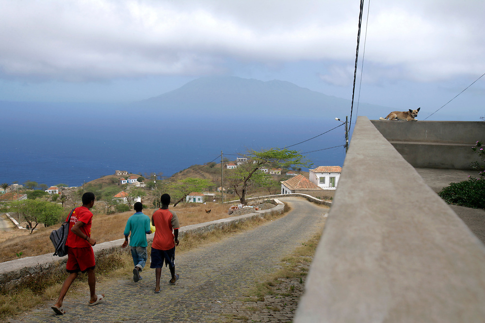 A dog sitting on a wall and boys walking in a cobblestone road are a common sight in Brava island, a place where the pace of time has always been slow.