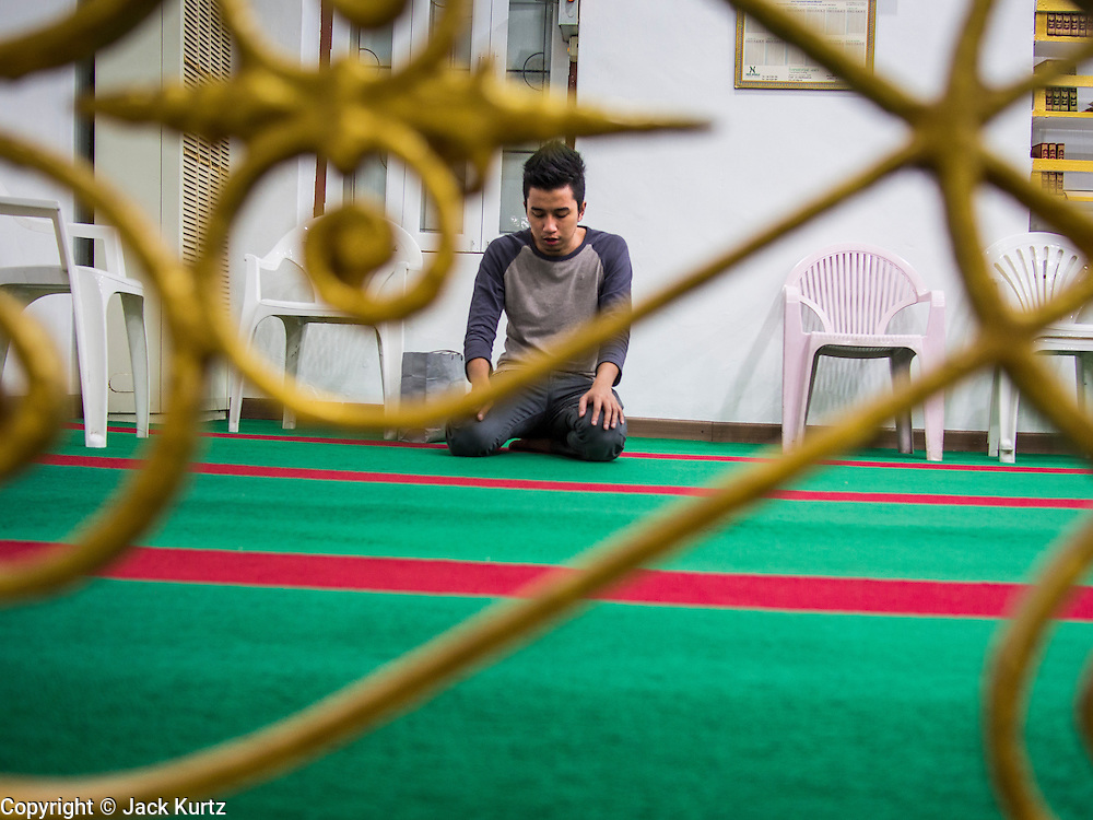 26 JULY 2013 - BANGKOK, THAILAND: A man prays in Haroon Mosque in Bangkok before Iftar. Iftar is the Muslim meal that breaks the day long fast during Ramadan. Ramadan is the ninth month of the Islamic calendar, and the month in which Muslims believe the Quran was revealed. The month is spent by Muslims fasting during the daylight hours from dawn to sunset. Fasting during the month of Ramadan is one of the Five Pillars of Islam. Muslims believe that the Quran was sent down during this month, thus being prepared for gradual revelation by Jibraeel (Gabriel) to the prophet Muhammad.     PHOTO BY JACK KURTZ