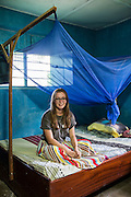 VSO ICS volunteer Rebecca Hastie sitting on her  bed in her host home. Volunteers stay with local families get the full experience. Lindi, Lindi region. Tanzania.