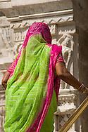 A sari clad woman entering a temple in Pushkar, Rajasthan, India