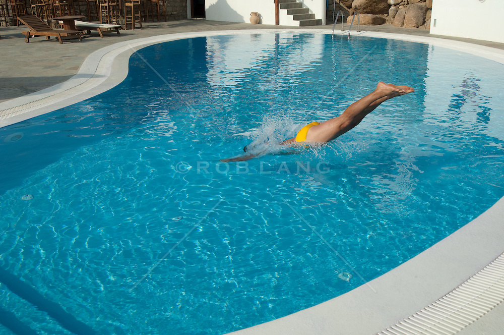 man in a speedo diving into a swimming pool