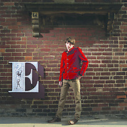 Young man standing on pavement in front of a letter E on a brick wall.