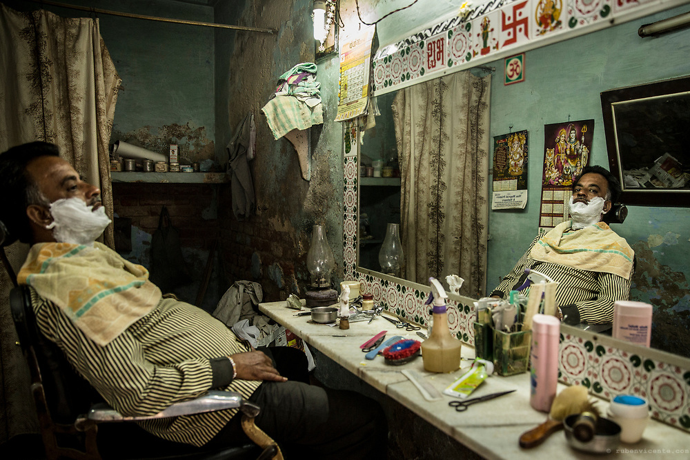 Man in a barbershop ready to be shaved. Mathura, India