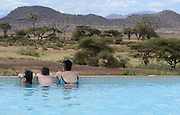 Kenya, Samburu National Park tourists in a pool at the lodge admire the landscape