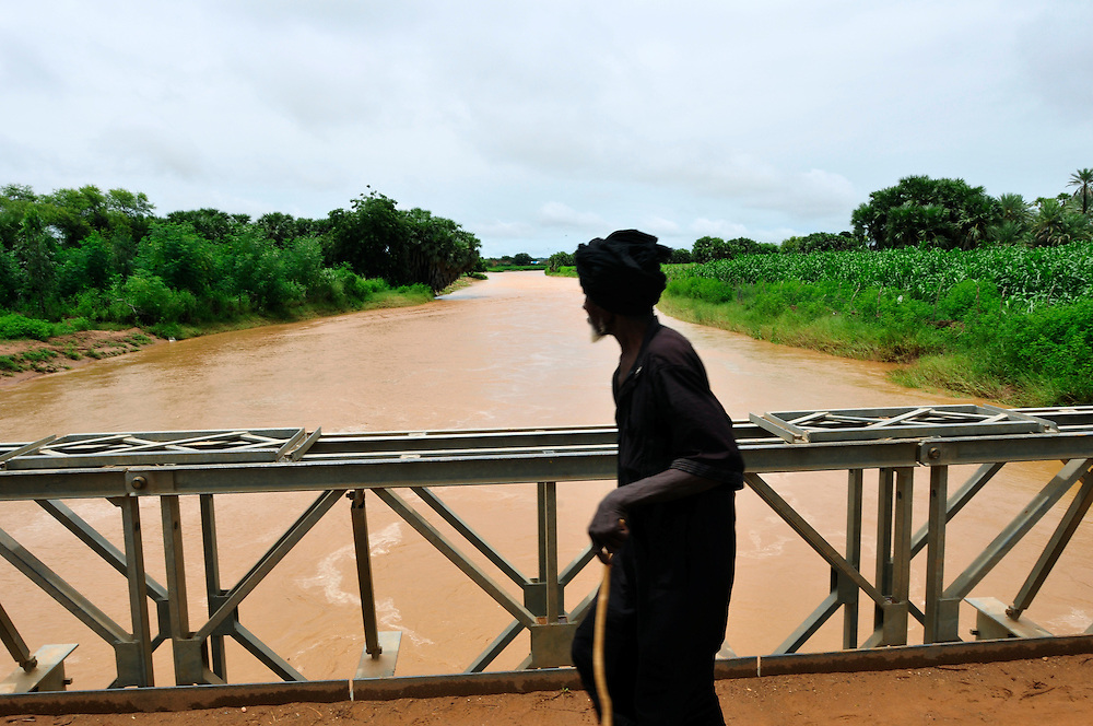 A man crosses a bridge over the Hospital Wadi after a torrential downpour. The Sahel region is prone to flooding and severe erosion during the rainy season due to a lack of infrastructure and water management systems. Much needed rain water rapidly drains off the land into rivers limiting seepage into the water table and benefits to agricultural production. <br /> Selibaby, Mauritania. 07/09/2010.