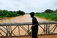A man crosses a bridge over the Hospital Wadi after a torrential downpour. The Sahel region is prone to flooding and severe erosion during the rainy season due to a lack of infrastructure and water management systems. Much needed rain water rapidly drains off the land into rivers limiting seepage into the water table and benefits to agricultural production. <br />