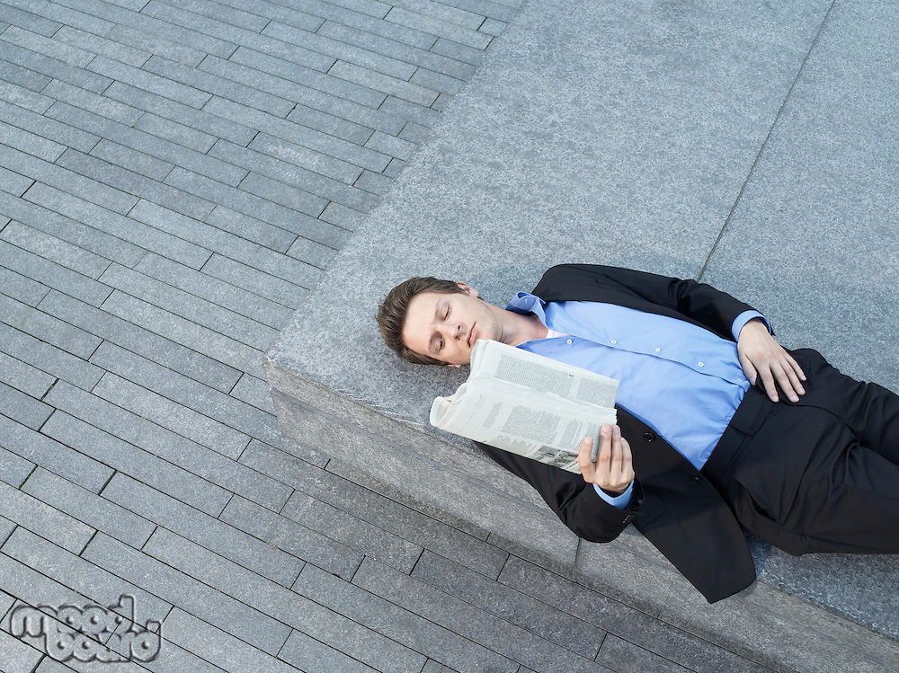 Young businessman lying on wall on pavement reading newspaper elevated view