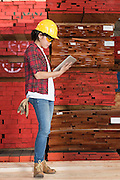 Side view of an Asian female industrial worker using tablet PC with stacked wooden planks in background