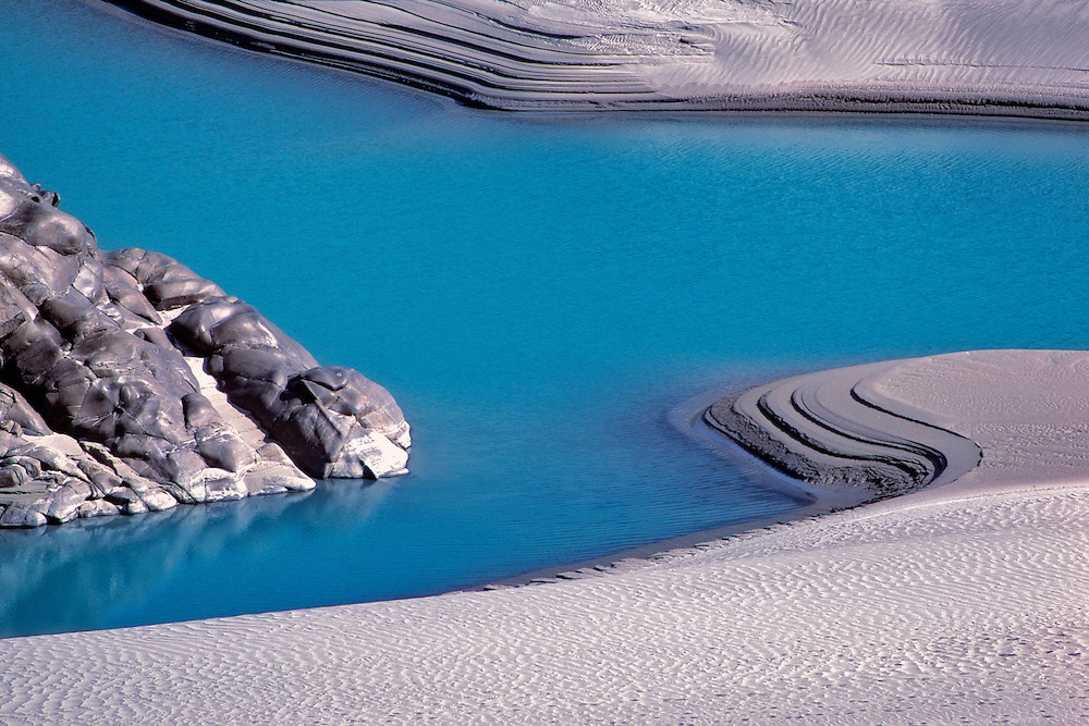 White sand contrasts with the blue water of the Indus River near Hunza, Pakistan.