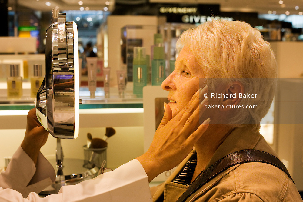 An elderly lady receives a consultation from professional beautician in Clinique Bar at World Duty Free in Heathrow Airport's T5