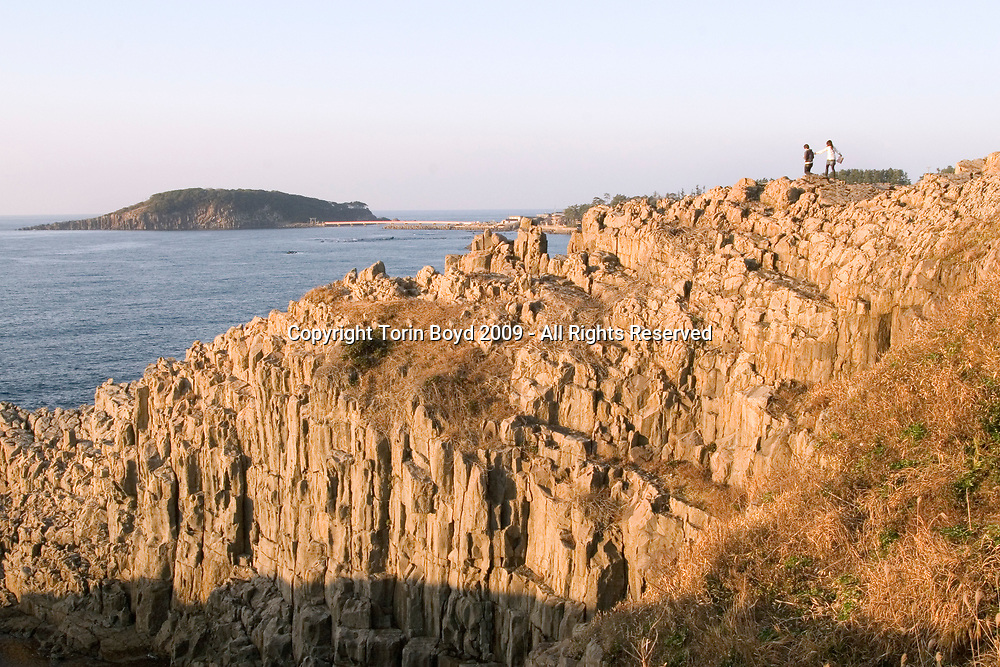 Nov. 26, 2009, Sakai City: Tourists sightseeeing at the rocky cliffs of Tojinbo, a popular tourist attraction on the Japan Sea coast that's also known for the number of suicide deaths that occur here. This scenic area known for it's coastal beauty, seafood and onsen hot springs resorts now adds suicide as a reason to come here. In 2008 twenty suicides occurred here, but this figure varies between Sakai City officials and a suicide help group dedicated to preventing suicides here. Called Kokoro ni Hibiku Bunshu Henshukyoku, this NPO founded in 2004 by retired policeman Yukio Shige (seen in this photo), who along with a group of volunteers patrols the cliffs on a daily basis to deter those contemplating jumping to their deaths. According to Shige, age 65, in the past five years since he founded his NPO, he is responsible for talking 222 people out of killing themselves. But even with Shige's efforts, the deaths here continue and as of late November, 2009, the current number of annual suicides at Tojinbo stands at thirteen. Japan has one of the highest suicide rates in the world and 2009 may surpass the record 34,427 deaths that occurred here in 2003. This increase is though to be a result of the Japanese recession which has been worsened by the global economic downturn. Depression is the number one cause for suicide in Japan, followed by illness and debt. Photo by Torin Boyd.