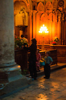 Our Lady of Chartres Cathedral, Chartres, France. Mother and two children watering the flowers in the Our Lady of the Pillar chapel.