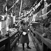 Bhutanese man crossing the bridge to the Taktsang Monastery (Tiger's Nest), Paro Valley, Bhutan, Asia