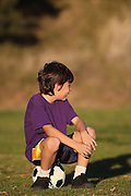 Boy sits on soccer ball looking to side in late afternoon sun - with copy space above