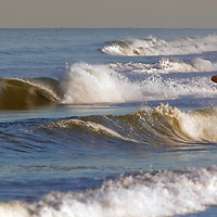 A surfer at Sandy Hook NJ looks to take advantage of waves left over from a nor'easter storm a day earlier.