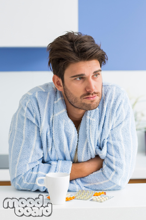 Young ill man with coffee mug and medicine leaning on kitchen counter