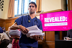 © Licensed to London News Pictures. 27/11/2019. London, UK. An NHS doctor hands out copies of an unredacted  report on trade negotiations with the United States that allegedly affects the NHS at a Labour Party event in Westminster. Photo credit: Rob Pinney/LNP