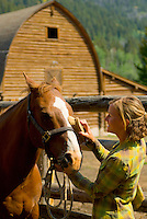 A young woman grooms her horse at a ranch in Wilson, Wyoming.
