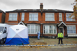 © Licensed to London News Pictures. 03/12/2013 London, UK. Police officers stand outside a house on the North Circular Road where a  teenager has been stabbed to death. Officers were called to the address  in Palmers Green where they found the 17-year-old from Haringey. Photo credit : Simon Jacobs/LNP
