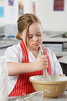 Girl (10-12) with Down syndrome using whisk to stir contents in bowl