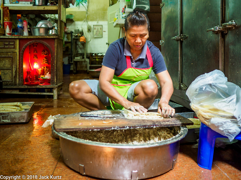 "07 FEBRUARY 2018 - BANGKOK, THAILAND: A woman in Bangkok's ""Chinatown""  makes minced pork snacks eaten during Lunar New Year celebrations. The Lunar New Year, also called Tet or Chinese New Year, is 16 February this year. The coming year will be the Year of the Dog. Thailand has a large Chinese community and Lunar New Year is widely celebrated in Thailand, especially in Bangkok and large cities with significant Chinese communities.      PHOTO BY JACK KURTZ"