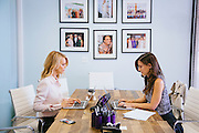 Kelly Sawyer Patricof and Norah Weinstein (brunette) work in the conference room at the Baby2Baby headquarters in Beverly Hills, California March 2, 2015.