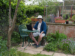 Man making a FaceTime call in the garden during Coronavirus lockdown. UK 2020 Model released