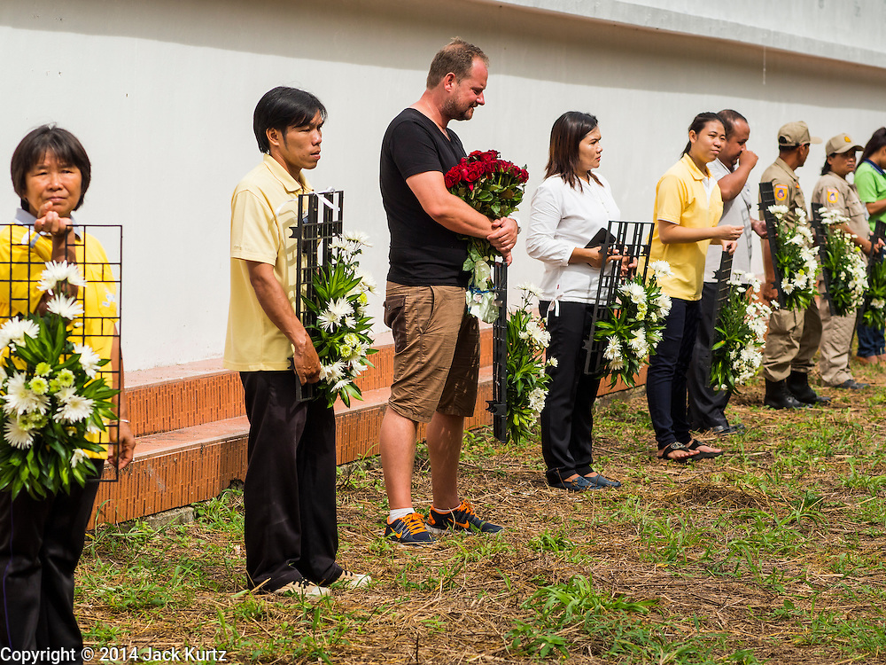 26 DECEMBER 2014 - MAE KHAO, PHUKET, THAILAND: DENNIS HOOGENKAMP (center, black tee shirt), from Amsterdam, Netherlands, holds flowers at the Tsunami Memorial Wall in Mae Khao, Phuket. Hoogenkamp said he was in Phuket during the tsunami. The wall is located at the site that was used as the main morgue for people killed in the tsunami and hosts an annual memorial service. Nearly 5400 people died on Thailand's Andaman during the 2004 Indian Ocean Tsunami that was spawned by an undersea earthquake off the Indonesian coast on Dec 26, 2004. In Thailand, many of the dead were tourists from Europe. More than 250,000 people were killed throughout the region, from Thailand to Kenya. There are memorial services across the Thai Andaman coast this weekend.    PHOTO BY JACK KURTZ