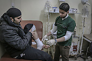 Dec. 29, 2015 - Aleppo, Syria - <br /> <br /> Syria Conflict<br /> <br /> Nour, a 18-year-old Syrian man, helps a wounded man in a hospital, in a rebel-controlled area of Aleppo, on December 29, 2015. Nour lost his leg following a bomb barrel attack by forces of Syria's President Bashar al-Assad near his house in Bustan al-Qasr district. A report from the Syrian Observatory for Human Rights (SOHR) claims that over 1,000 children have been killed in airstrikes during the nation'ongoing civil war, an additional 1.5 million people have been wounded for life in the airstrikes that have been carried out by Syria' government since the Syrian conflict.<br /> ©Exclusivepix Media