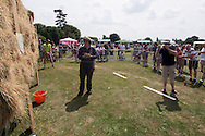 Photo by Andrew Tobin/Tobinators Ltd - 07710 761829 - Victor Kronig of Cambridge and Switzerland takes aim during the World Peashooting Championships held at Witcham, Cambridgeshire, UK on 13th July 2013. Run in conjunction with the village fair, the Championships have been held in Witcham since 1971 when they were started by a Mr Tyson, the village schoolmaster, in order to raise funds for the village hall.Competitors come from as far afield as the USA and New Zealand to attempt to win the event. The latest technology is often used, including laser sights and titanium and carbon fibre peashooters. All peashooters must conform to strict length rules, not exceeding 12 inches, and have to hit a target 12 feet away. Shooting 5 peas at a plasticine target attached to a hay bale, the highest scorers move through the initial rounds to a knockout competition, followed by a sudden death 10-pea shootout.